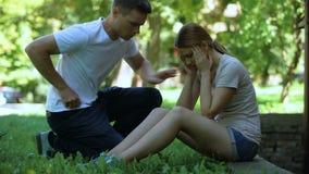 Sufrimiento de la muchacha de la jaqueca, sentándose en parque, hombre que llama la ambulancia, primeros auxilios metrajes