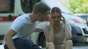 Sufrimiento de la mujer del dolor de cabeza, ambulancia no indiferente de las llamadas del hombre, primeros auxilios almacen de metraje de vídeo