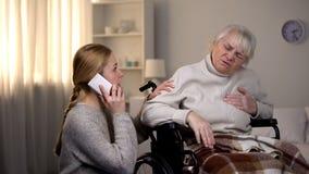 Sufrimiento de la mujer mayor del ataque del corazón, nieta que llama la ambulancia, salud foto de archivo libre de regalías