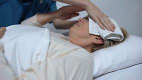 Sufrimiento enfermo de la mujer de la fiebre y desvarío, enfermera que pone la compresa en la frente metrajes