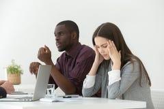 Sufrimiento femenino subrayado del dolor de cabeza durante la reunión de negocios fotos de archivo