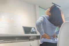Sufrimiento joven de la empresaria del dolor de espalda en oficina foto de archivo libre de regalías