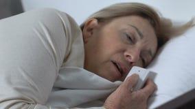 Sufrimiento paciente femenino del dolor que empuja el llamada-botón, necesitando ayuda, hospital metrajes