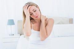 Sufrimiento rubio trastornado del dolor de cabeza y del dolor de cuello imagen de archivo libre de regalías