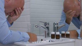 Sufrimiento y hombre decepcionado en el cuarto de baño que toma píldoras y las drogas imagen de archivo libre de regalías