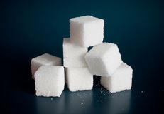Sugar. Sugar cube on a dark blue background Stock Photography