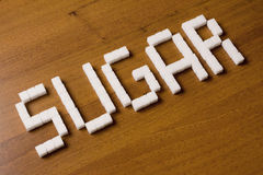 Sugar. The word made of cubes of sugar, laid out on a wooden surface Stock Photo
