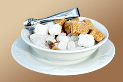 Sugar. Beet and cane sugar in sugar-basin with pincers Royalty Free Stock Images