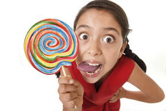 Sugar addict latin female child holding big lollipop candy eating and licking happy crazy excited Stock Photography