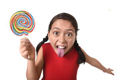 Sugar addict latin female child holding big lollipop candy eating and licking happy crazy excited Stock Images