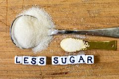 Less sugar advice written with ceramic cubes with letters near the big and small sugar pile. Dieting concept. royalty free stock photography