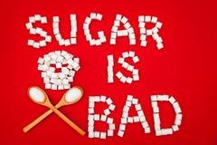 Sugar is bad sign from sugar cubes. Sugar is bad sign made from sugar cubes on red background Stock Photo