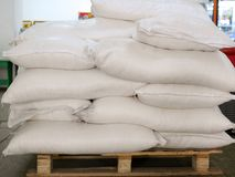 Sugar in bags, stacked on wooden pallet stock image