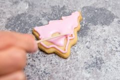 Sugar baker work step, pink royal icing or frosting on a christm stock photography