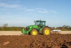 Modern John Deere tractor pulling a plough Stock Image