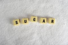 Sugar block letters in crossword over sugar pile isolated on grainy white sugar texture in sweet food abuse Royalty Free Stock Photo