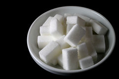 Sugar bowl. White ceramic sugar bowl with sugar cubes in black background Royalty Free Stock Photos