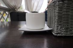The sugar bowl stands on a wooden table next to a wicker basket for appliances as a background stock photo