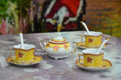 Sugar bowl and three teacups on the table stock photos