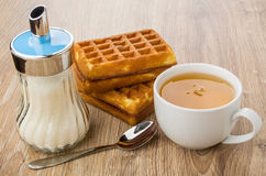Sugar bowl, wafers stuffed, cup of tea and spoon Stock Photography