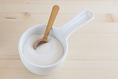 Sugar bowl with a wooden spoon. On the wooden table Royalty Free Stock Photo