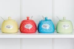 Sugar Bowls colorido en un estante blanco imagenes de archivo