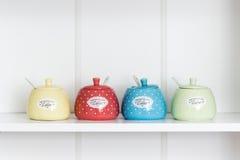 Sugar Bowls colorido en un estante blanco fotos de archivo