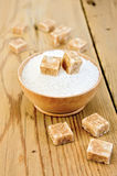 Sugar brown and white in a wooden bowl on a board Royalty Free Stock Images