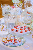 Sugar cake on desert table. Sugar cake with berries macaroon and flowers on table at wedding stock photos