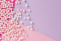 Sugar candy scattered on pastel colored background Stock Photos