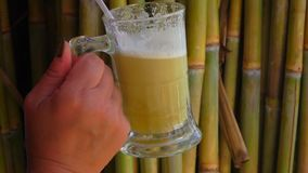 Sugar cane juice. From stems in a transparent mug with a straw stock video footage