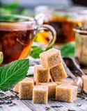 Sugar. Cane sugar. Cane sugar cubes heap close up macro shot. Tea in a glass cup, mint leaves, dried tea, sliced lime, cane brown Stock Photos