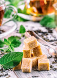 Sugar. Cane sugar. Cane sugar cubes heap close up macro shot. Tea in a glass cup, mint leaves, dried tea, sliced lime, cane brown Royalty Free Stock Images