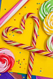 Sugar canes in a heart-shape and other sweets Stock Images