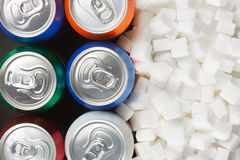 Sugar in carbonated drinks. Unhealthy food concept - sugar in carbonated drinks. Sugar cubes as background and canned drink Royalty Free Stock Photo