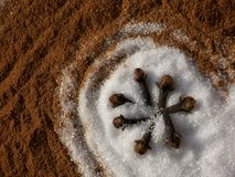Sugar on Cinnamon with Cloves. Close up of white granulated sugar on cinnamon, with cloves placed in the shape of a star Royalty Free Stock Photo