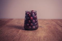 Sugar coated balls in glass container. A glass conttainer filled with sugar coated purple sweet balls stock photography
