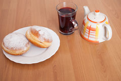 Sugar coated doughnuts, a glass of fruit tea and tea pot on white plate on brown wooden background royalty free stock images