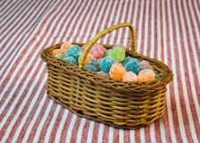 Sugar coated jelly sweets in wicker basket on striped tablecloth. Sugar coated jelly sweets in wicker basket on red striped tablecloth Royalty Free Stock Images