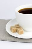 Sugar and coffee. White cup of coffee with brown lump Royalty Free Stock Photo