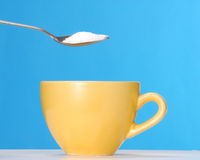 Sugar coffee. Pouring sugar on a yellow cup Royalty Free Stock Photo