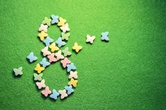 Sugar colored butterflies on a green rough surface, in shape of number eight, concept of March 8, with copyspace stock photo