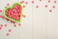 Sugar hearts in a baking dish. Congratulatory background. Sugar confetti on a white wooden table. Valentine`s Day Stock Photos