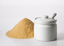 Sugar container. Heap of brown sugar beside container in white background Royalty Free Stock Photo