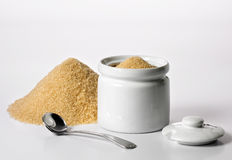 Sugar container. Next to heap of brown sugar. Cover and spoon removed. White background stock images