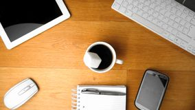 Sugar cube falling into cup of coffee next to tablet pc and smartphone stock video footage