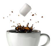 Sugar cube falling and splashing into a cup of black coffee. Close-up view. Sugar cube falling and splashing into a cup of black coffee. Close up view. At white Stock Images