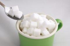Sugar cube in green tea cub Stock Images