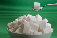 Sugar cube on a spoon. White subar cube ona s spoon above a bowl full ob sugar Stock Photos