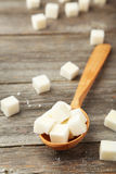 Sugar cube in spoon on grey wooden background Stock Image